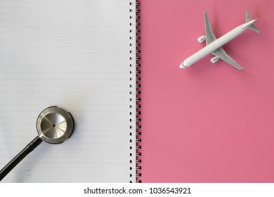 Jet Commercial Airplane Model and Stethoscope on Pink Cover of Note Book. Copy Space for Text. Idea Concept for Medical Flight or Health Travel Insurance