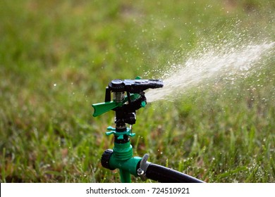 a jet and a drop of clean water while watering the grass of a green lawn