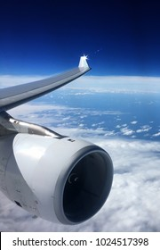 Jet engine and wing an airbus a340 flying at 30,000 feet above white clouds and dark blue sky