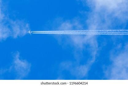 A jet flies across a blue partly cloudy sky leaving vapour trails