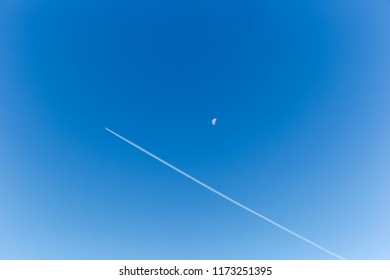 A jet flying beside the moon on a crystal clear day.