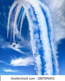 A jet Flying Team, single seat jet  airplanes flying in close formation with vapor trails at an Oregon air show.