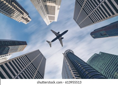 Jet plane aircraft traveling in the sky over city buildings in downtown travel destination of Singapore City. Showing concept of tourism transportation, airplane manufacturing and airline business.