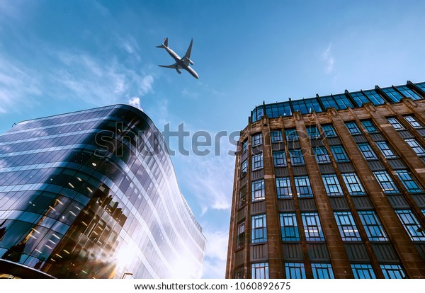 Jet plane aircraft traveling in the sky over the center of Glasgow city buildings.
