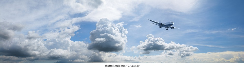 Jet plane in a blue cloudy sky is maneuvering for landing. Panoramic composition in high resolution.