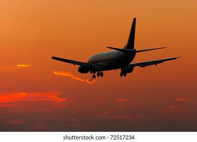 Jet plane landing in sunset