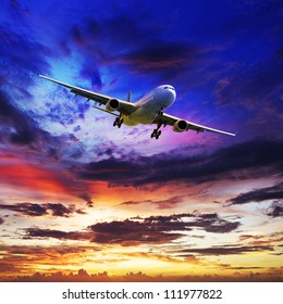 Jet plane is maneuvering for landing in a spectacular sunset sky. Square composition.