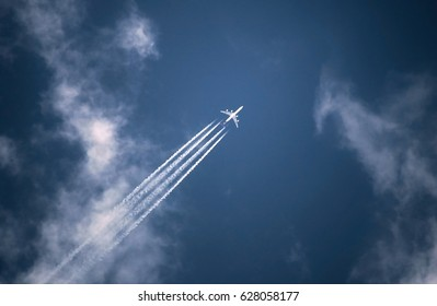 Jet plane pulling white contrails in  blue sky. Airliner trail while transports passengers