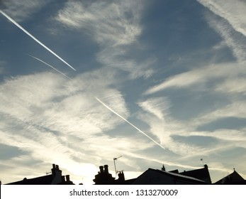 Jet planes airliners leaving trails in the sky. Vapour trails in cloudy sky early mornings no in February with silhouette of roof of building