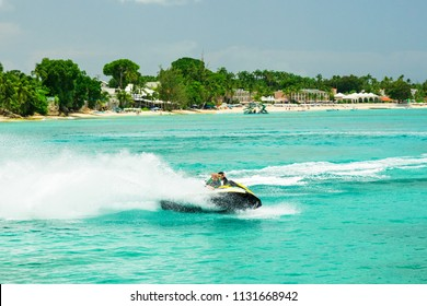 Jet ski rider on tropical pristine beach in Barbados, Carribean