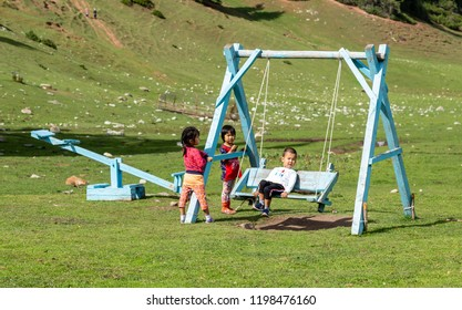 "Jeti Oguz, Kyrgyzstan - March 22, 2018: Three Asian children ride during the national holiday ""Nauryz"" on a wooden swing."