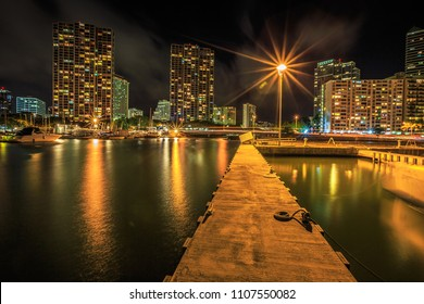 Jetty in Ala Wai Harbor, the largest yacht harbor of Hawaii. Honolulu Harbor skyline reflecting in the water at night near the popular Waikiki Beach, Oahu, Hawaii.