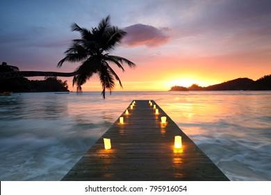 Playa de mar al atardecer con velas, vacaciones románticas en Seychelles