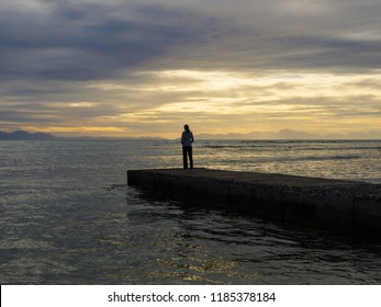 The jetty at Bikini Beach in Gordon's Bay, Western Cape, South Africa. A single woman stands at the end of the jetty and looks out to sea as dusk. The sea is calm and tranquil