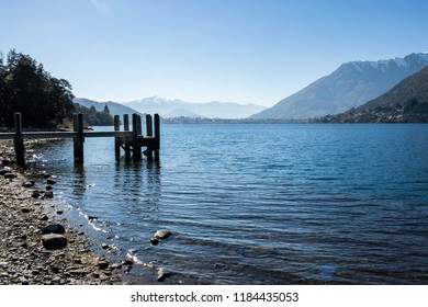 Jetty in a lake with mountains in the background