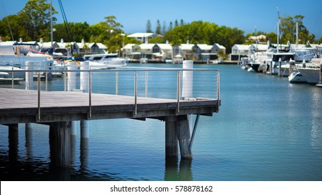 Jetty in a Luxuries Marina with Pristine Blue Water and Sailing Boats in the Background During a Sunny Day, Hope Island, Gold Coast, Queensland, Australia