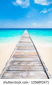 Jetty on a beautiful island in the caribbean with white sand and blue sea
