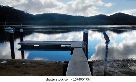 Jetty on calm reflecting water, Patonga Australia