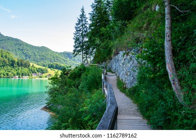 Jetty on the edge of the turquoise lake called Wolfgangsee mountains in the background and clouds on the sky