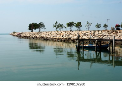Jetty with piles of rocks was built for waves protection, at a coast of Thailand. A small boat was embarked behind a pier. The shadow of jetty, tree & surroundings are reflecting on water surface.