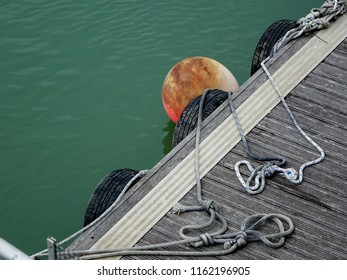 A Jetty Walkway, Showing a Buoy and Protection Tyre Fenders with Rope Slip knots and Tails on Wooden Non-Slip Planks.