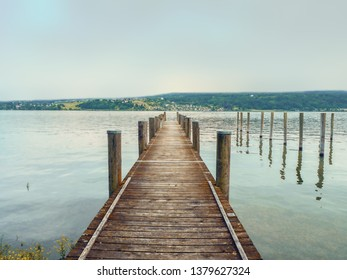 A jetty of wooden planks protrudes into Lake Constance (Germany). The almost light turquoise evening sky is reflected in the water, on the opposite side you can see a strip of land.