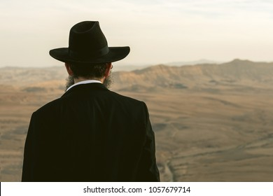 the Jew stands on the edge of the breakaway and looks at the beautiful mountains