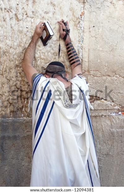 Jew in tallith prays in the western wall in Jerusalem.