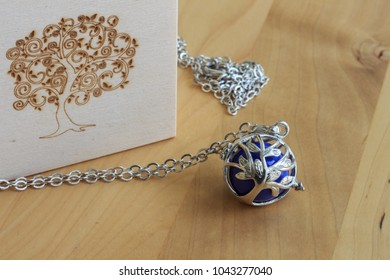 A jewel to represent the tree of life. A silver caller pendant as a gift for a pregnant woman. Objects on the background of a brown wooden table.