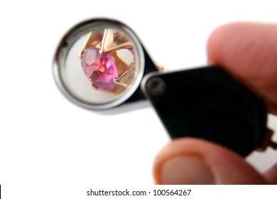 Jeweler with magnifying glass examine the jewel