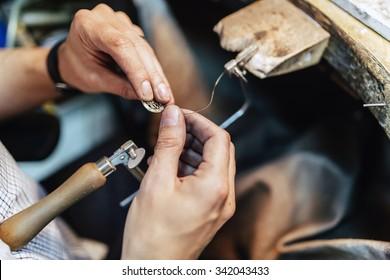 Jeweler making jewelry on workbench