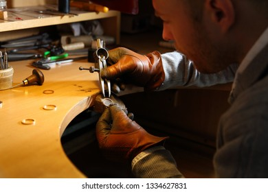 Jeweler measuring a ring with compass divider in a workshop lith with warm light