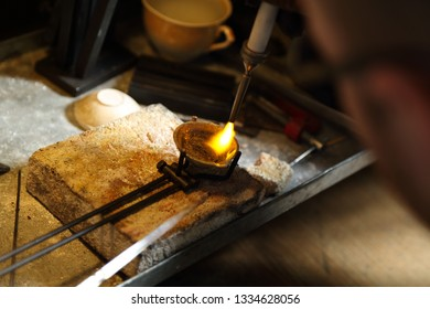 Jeweler melting precious metal with hydrogen burner
