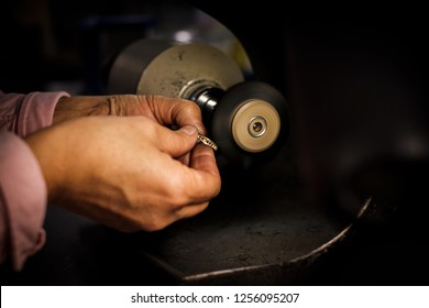 Jeweler polishes a gold ring on a bench grinder in an authentic jeweller's workshop