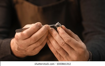 Jeweler repairing ring with gem, closeup