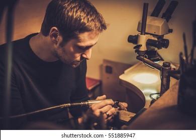 Jeweler at work in jewelery workshop.