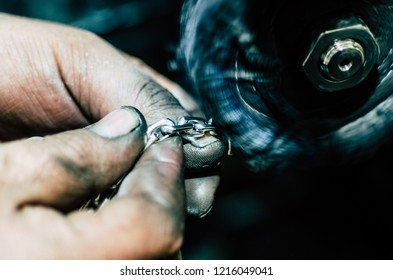 Jeweler working on silver chain in his workshop. Detail of silver polishing.