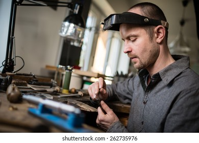 Jeweler working on wedding gold ring in his workshop looking at the camera.