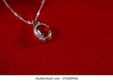 jewelery luxury ruby pendant on a red silk background