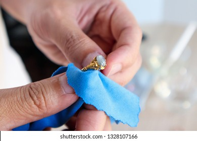 Jeweller hand polishing and cleaning gold jewelry ring with micro fiber fabric