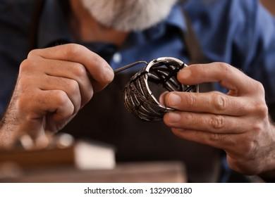 Jeweller making beautiful bracelet in workshop, closeup
