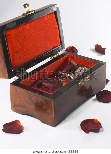 Jewellery box, with rings and brooches and rose petals.