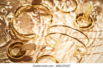Jewellery branding, fashion gift and luxe shopping concept - Golden bracelets, earrings, rings, jewelery on gold water background, luxury glamour and holiday beauty design for jewelry brand ads