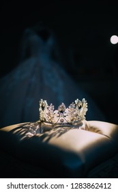 jewellery and magical diamante crown on the pillow and wedding dress on the background. Royal wedding concept. Princess concept. Bridal accessorizes. Beauty contest winner. Tiara wedding
