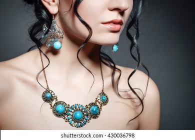 Jewellery on a girl. Large jewelry with turquoise stones. Earrings in the form of a butterfly on a girl