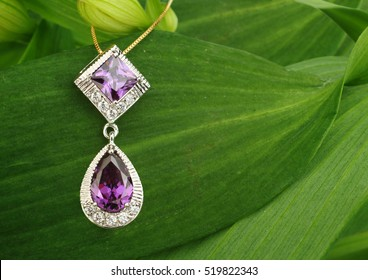 Jewellery pendant with diamonds and spinel on green leafs background