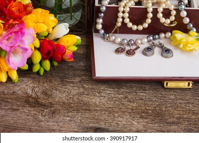 Jewellery in treasure box with fresh fresia flowers border on wood