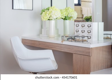 Jewelry accessory and jar of flower on white top dressing table