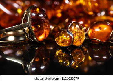 jewelry with amber stones, amber necklace ring and earring and pendant with noble metal like gold, in front of a black background on a black stone with reflection