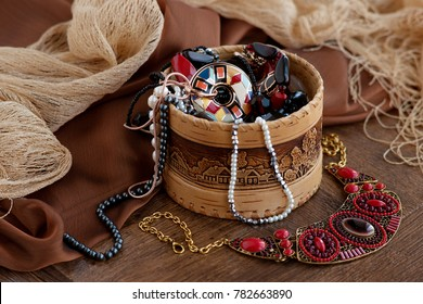 Jewelry in the background of silk. A lot of jewelry in the box. Design and bijouterie. Jewelry is surrounded by a delicate silk fabric. Pearls, pendants, necklaces as accessories.